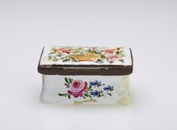 Small snuff box with white ground and sprays of flowers on the sides, the pierced lid with a basket overflowing with flowers in relief, with metal mounts.