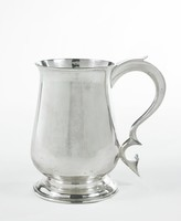 Small plain silver mug of modified baluster shape with flared lip, with splayed, stepped round foot and double scroll handle that terminates in a heart-shaped rest.