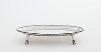 Small silver, oval tray on four cast ball and claw feet, with beaded edge.