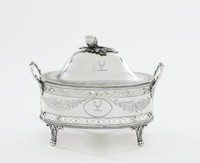 Small covered dish in silver, originally with glass liner, resting on four leafy ball feet, the lower and upper edge of the body with a band of beading, the body with a narrow band at top and bottom in a pierced guilloche pattern – repeating, interlacing curved bands enriched with rosettes – the central body decorated with bright-cut engraving, on each side a central oval reserve flanked by floral garlands, on one side the reserve engraved with a stag's head cabossed (crest associated with many different families), on the other with a flower and leaf motif, with two loop handles that terminate in leafage, the domed cover engraved at the edge with a band of leafy motifs, with acorn and oak leaf finial.