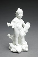 """Small figure of a reaper or an allegory of autumn made of white soft-paste porcelain covered with a clear, lead-based glaze, in the form of a naked putto or cherub leaning against a coral-like """"stump"""" and draped with a cloth that is belted at the waist, standing on an irregular, rocky base, under his left arm he holds a thick sheaf of wheat, his right arm is raised and outstretched and in his right hand he holds something, which has broken off (perhaps a sickle)."""