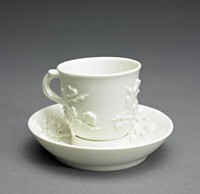 Cup and matching saucer of white porcelain decorated with applied sprays of prunus blossoms in the manner of blanc-de-chine, the saucer with raised center rim to accommodate the cup with its raised base, the cup with twig handle.