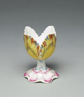 Small, delicate egg cup in the form of a tulip with splayed foot highlighted in puce, stem highlighted in blue and the egg cup itself comprised of four yellow petals feathered in shades of brown, black and blue.