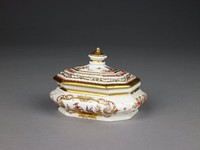 """Small, oblong, octagonal sugar box of white porcelain with gilding, painted with small reserves on the sides with Chinoiserie scenes inside (a Chinese figure preparing tea on one side and a Chinese figure with a bird and cage on the other), """"indianische Blumen"""" are scattered over the rest of the box, the cover likewise painted with Chinese figures, one with bells, the other preparing tea, with wide gilt and scrollwork borders as well as a Chinese-inspired floral border, the finial in the shape of a pagoda."""