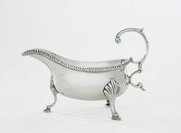 Delicate silver creamer with low, tub-shaped body resting on three hooved feet terminating in splayed leafy elements, with long extended spout and beaded edge, the double C-scroll handle with small thumb rest.