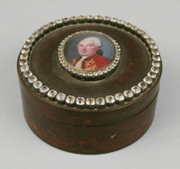 Round box with miniature on top surrounded by rhinestones around inner and outer edges.