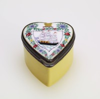 Snuff box of enameled copper in the shape of a heart, the bottom yellow and the lid with white ground and a shield containing a three-mast ship with blue flag, the shield surrounded by a garland of flowers, at the top a crest with a sheaf of wheat, with metal mounts.