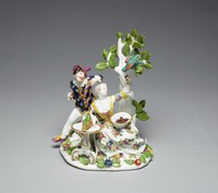 """Porcelain Commedia dell'arte figural group of a Harlequin wearing a lilac conical hat, a white ruff over a gilt-edged jacket half patterned with yellow, lilac and black diamonds and the other half blue and patterned with playing cards, with large gold buttons, with white trousers and lilac shoes with big yellow bows, in his left hand he holds cherries, he kneels behind his female companion Columbine, who wears a lilac and yellow bodice and white skirt decorated with bright """"indianische Blumen"""", seated with a basket of cherries on her lap, her right hand by a colorful green parrot perched on a gilt-edged, white tripod table, her left hand and gaze raised toward a second parrot perched on a leafy branch of the tree behind them, the mound base applied with colorful flowers and green leaves."""