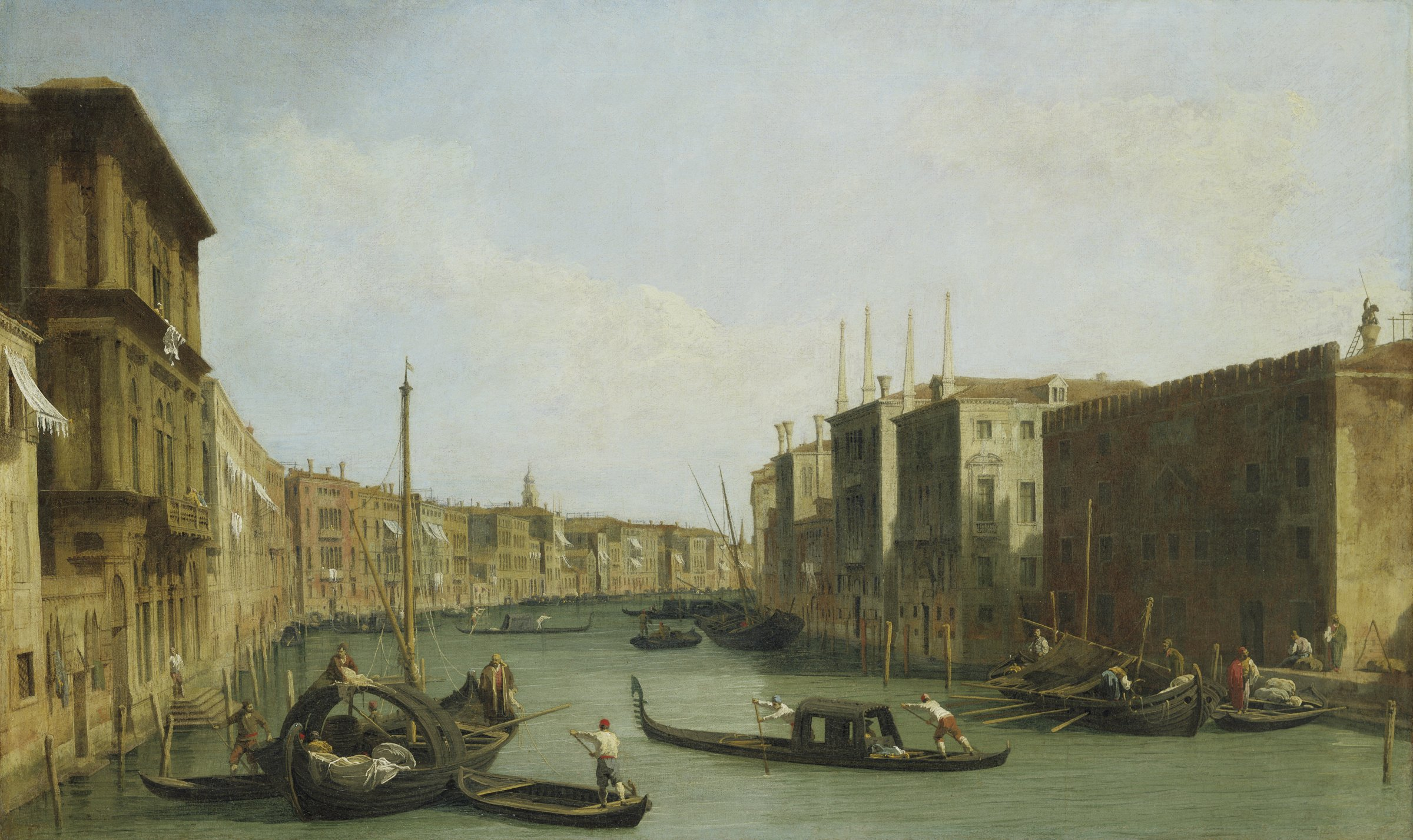 In this sweeping view of a Venetian canal with historic buildings on either side, gondolas laden with passengers are being steered by their gondoliers.