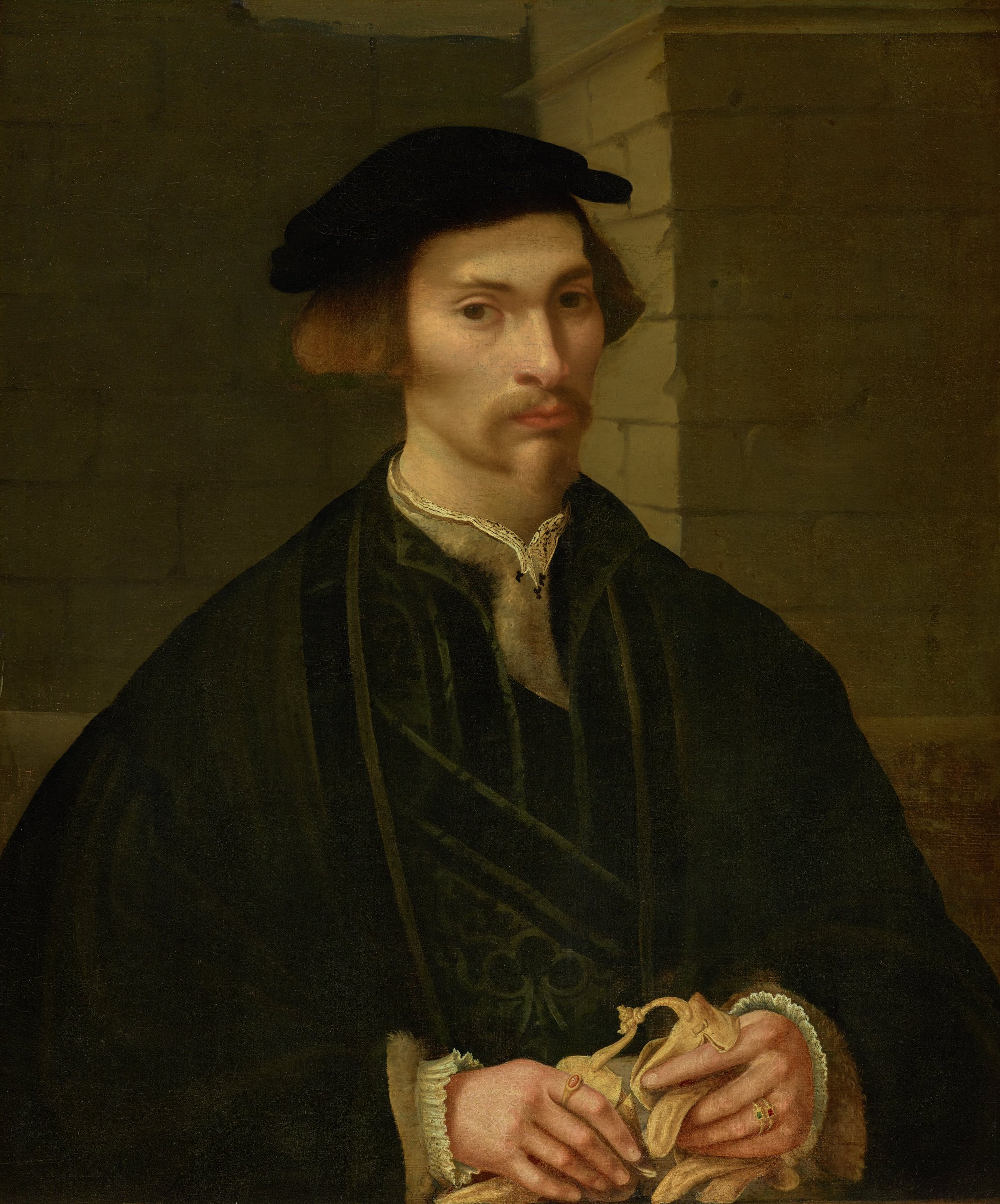 In this three-quarter length portrait, a man is pictured wearing a dark colored hat and holding a pair of white gloves.