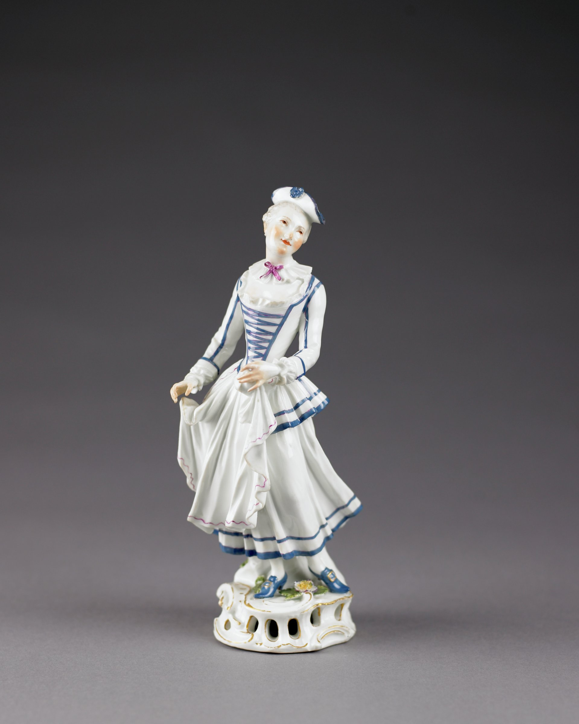 The figure of Pierrette standing on a rocaille base with pierced and gilded scrolls, the base decorated with small applied flowers with green leaves, Pierrette wears a costume in white consisting of a full skirt and a laced bodice trimmed in blue with iron red, with a ruffle collar tied with a lilac bow, her white apron trimmed in iron red, on her head a white tricorn hat with blue edging and flower, both hands are lowered to her apron and she stands with left leg behind and leaning slightly left as if in movement, her shoes are blue with gilt buckles