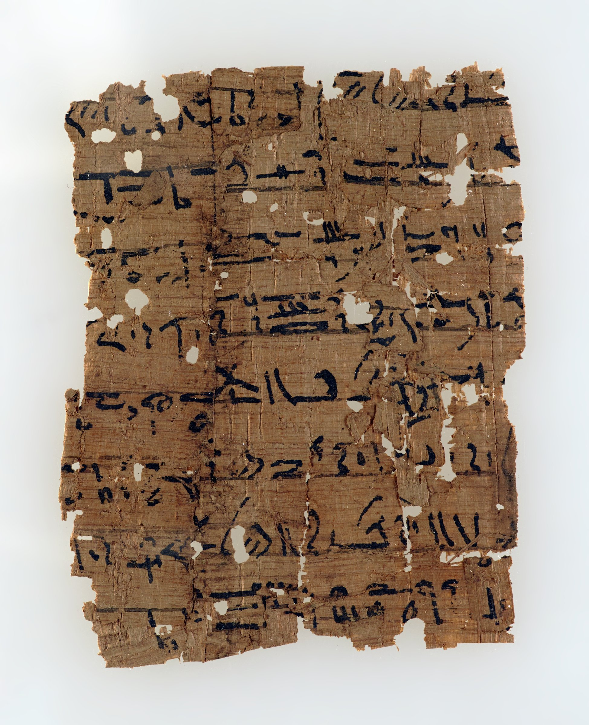 Papyrus witten in a mix of Hieratic and Demotic script. A piece on the left has been joined incorrectly (upside down) and some stray fragments on the surface of the right side are also obscuring the view of the text making an identification of the text difficult. It appears to contain a magical-medical text.