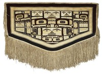 Wearing blanket in basic shape of a rectangle, with bottom side of rectangle in a shallow downward V-shape; long fringe from warp threads extend from bottom. Bilaterally symmetrical patterns fill the space, composed of abstracted animal faces and other zoomorphic design elements.
