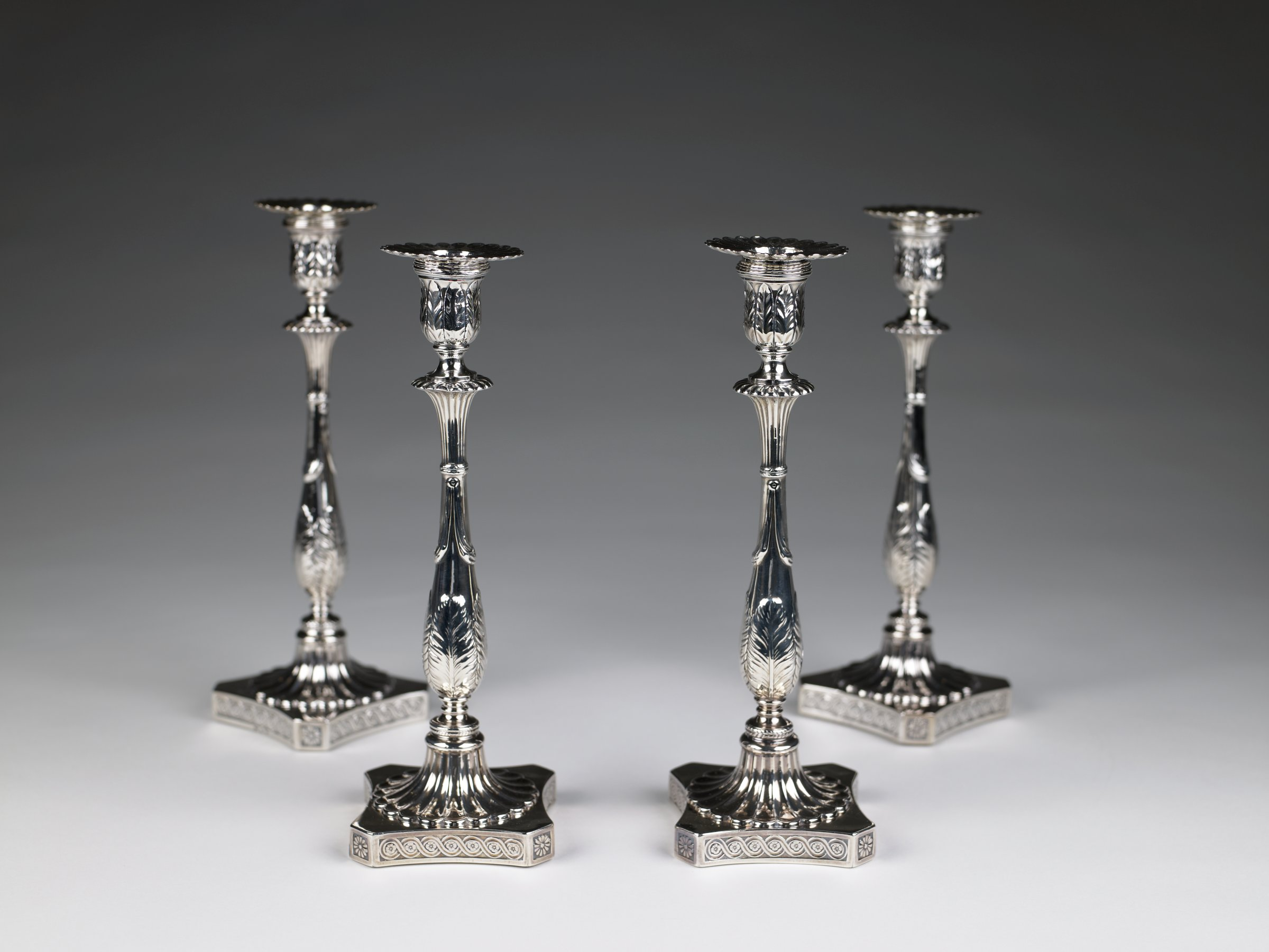 Rare set of four silver candlesticks each on a square plinth with canted corners chased with guilloche on the sides and flowers on the edges, the fluted foot rises to a baluster-shaped stem decorated with palmetto leaves and swags, the upper stem likewise fluted and supporting an urn-shaped socket decorated with similar leaves, with removable fluted nozzle