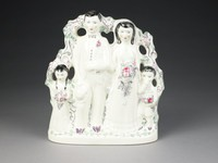 Large figural group of white earthenware and highlighted sparsely with bright enamels modeled in the manner of 18th-century Staffordshire figures of a bride and groom with a flower girl and ring bearer, the bride is pregnant and holds a large bouquet at waist height, the groom holds a hat in his right hand, the young boy blows his nose on the bride's veil, behind the couple is a tree with flowering branches and on the reverse are animals such as a squirrel, a bird's nest with three chicks and a mother bird, and a rabbit amongst the foliage; incised in the trunk of the tree are two hearts with an arrow through them and the initials of Josiah Wedgwood V and others who contributed to the production of the piece.