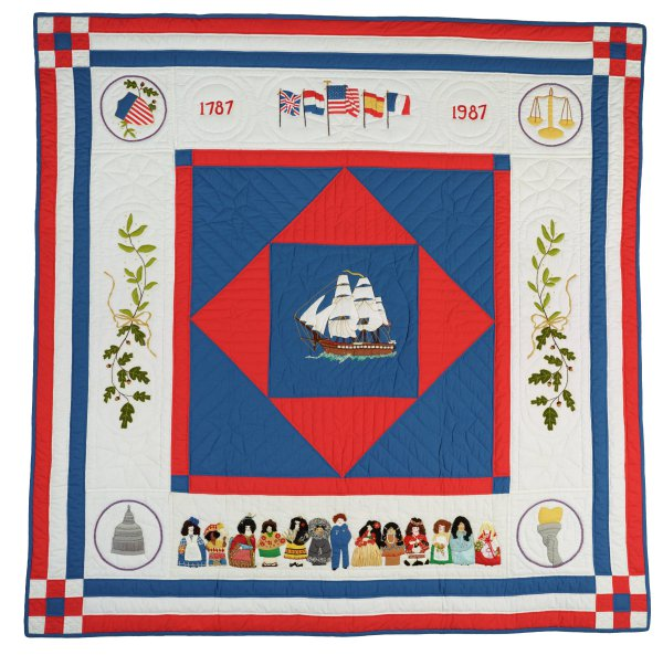 Large, mostly red, white and blue cotton embroidered and appliqued quilt designed to commemorate the bicentennial of the signing of the US constitution in 1787, in the center a blue square edged in red and with a smaller red square at an angle inside it, within this a blue square with the image of a full-rigged ship on its way to the New World, at each corner a roundel that includes representations of the three branches of the United States government as well as liberty illustrated by a torch in the lower right corner, at the top are the dates 1787 and 1987 and the American flag flanked by the flags of the four European countries that contributed to the early European settlement of North America: Great Britain, Spain, the Netherlands, and France, along the sides are olive branches signifying peace, and along the bottom of the quilt are thirteen individuals in native or traditional dress representing the diversity of the United States.