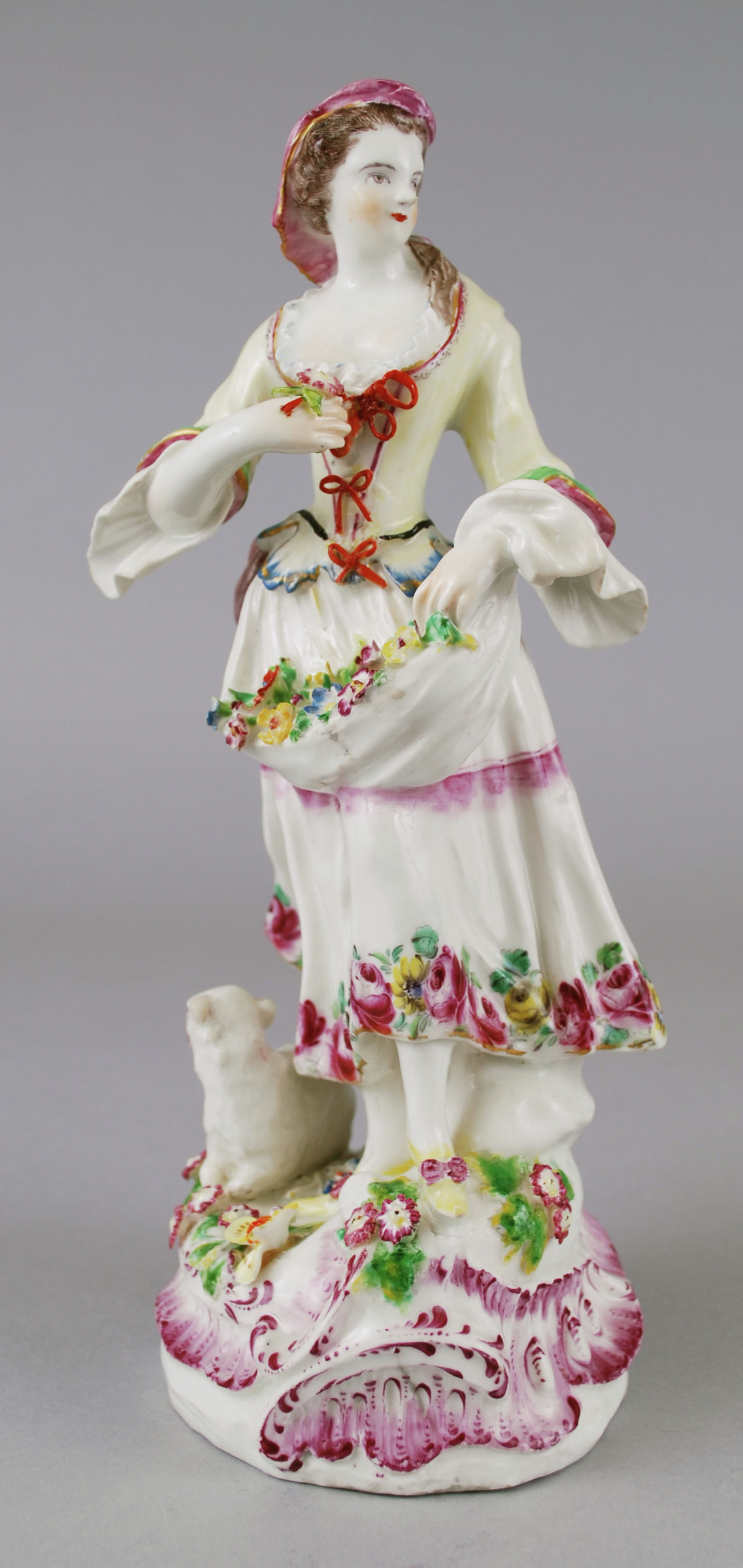 A soft-paste porcelain figural group of a standing female and seated on the ground near her feet is a lamb facing the opposite direction. The female figure is in a dress with painted flowers along the hem, with flowers at her feet. Her arms are bent outward, one arm lower with the apron's end draped over it is filled with flowers, while other hand holds a bouquet closer to her chest. The figural group is on a decorated scroll base painted in burgundy.