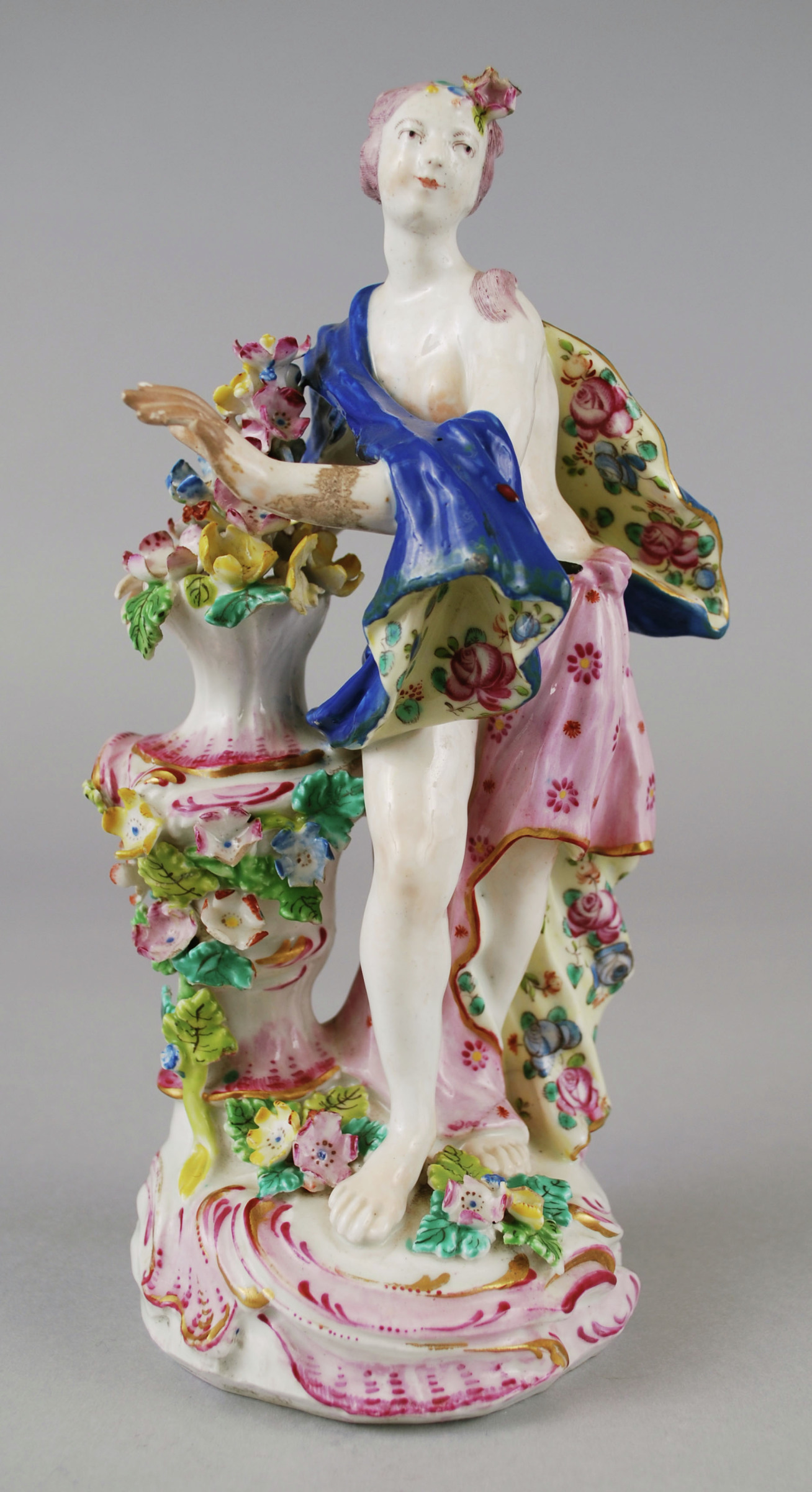 Bow porcelain female figure 'Spring.' She stands on a circular rococo base with painted scrolls in burgundy and gold. She is draped in a fabric painted in a floral pattern from one side and blue on the other side. On one side of her is pedestal decorated with flowers and leaves. There is also a hole in back for bocage or candlestick.