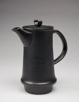 Coffee pot with a cylindrical form. The pot's form flares out at the bottem and then tapers to the base. The exterior is decorated with plain, impressed bands and is matte black. The pot's handle is rounded and placed at an angle to the pot's body. The pot's spout is wide at its base and becomes narrow. The lip of the pot extends inward, then drops and extends again for the pot's lid to rest. The pot's lid is circular with an exaggerated 'u' shape in its center.