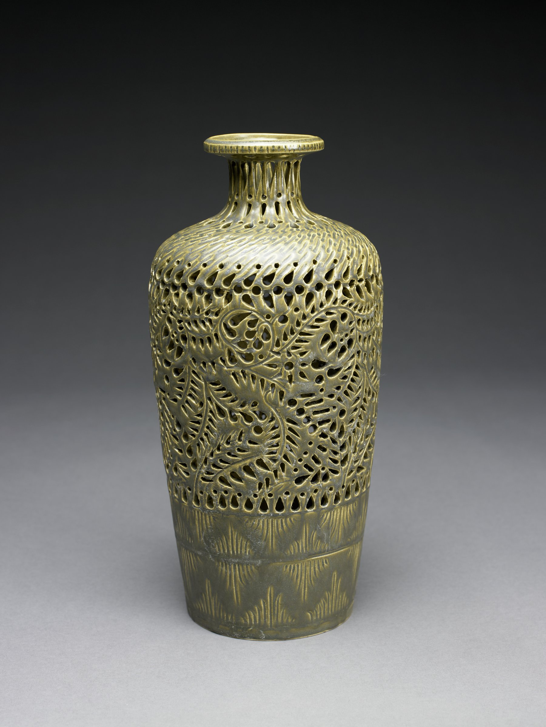 Tall, bottle-shaped bone china vase covered with a khaki-greenish glaze, the lower body incised and glazed in a chevron pattern, the upper two-thirds of the body and narrow neck pierced in a pattern of swirling foliate motifs, the lip slightly flared.