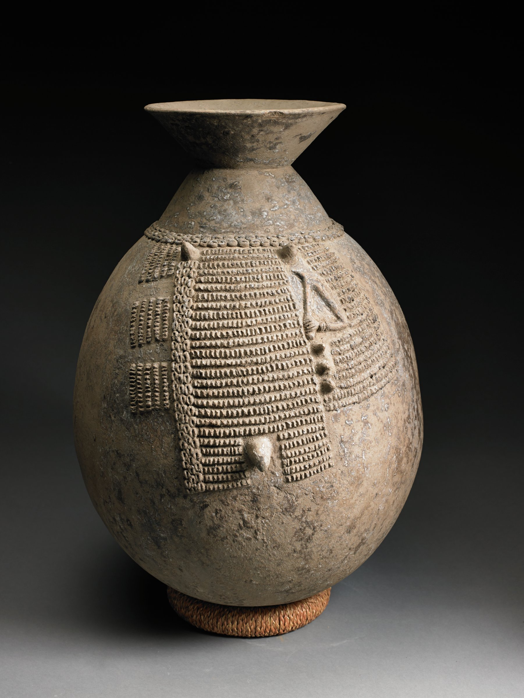 Brown, ovoid vessel has narrow neck and rim that flares at an angle. Body has rectangular sections of raised bumps, possibly breasts and umbilicus, and appliqued bent arm holding tool.