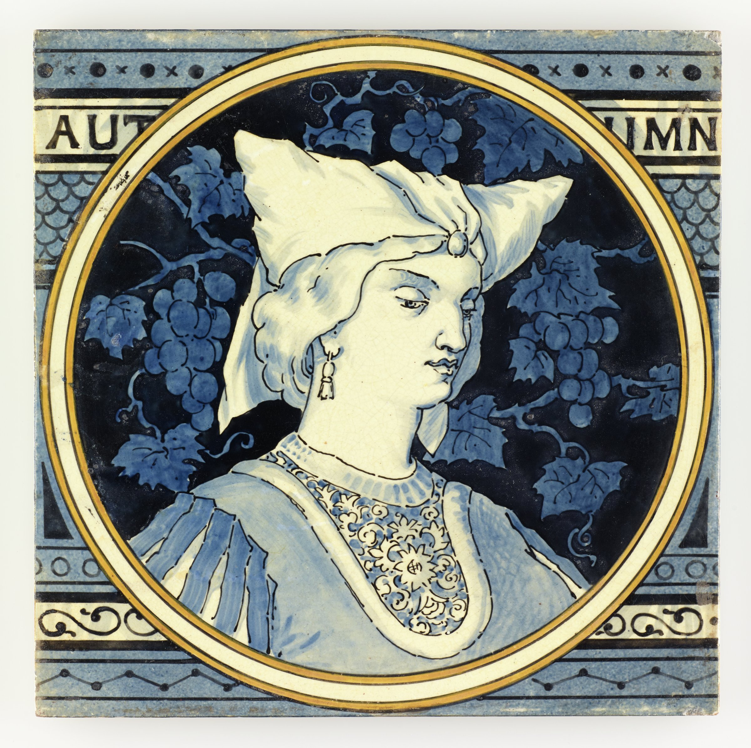 Large, square earthenware tile partially printed and hand-painted with a circular reserve outlined by a white band within two yellow bands containing in white with blue highlights the portrait of a woman facing slight right wearing Medieval garb with a pointed headdress and earrings, the ground with a blue on blue design of grape vines with bunches of grapes, the larger ground of the tile contains in various shades of blue a pattern of decorative, horizontal bands with from the top a band of small x's and solid dots; the name of the season AUT UMN; a fish scale pattern; a band of open dots; a band of scrolling motifs; and a band featuring a zigzag design, the reverse with horizontal bars in relief to aid adhesion when setting the tile.
