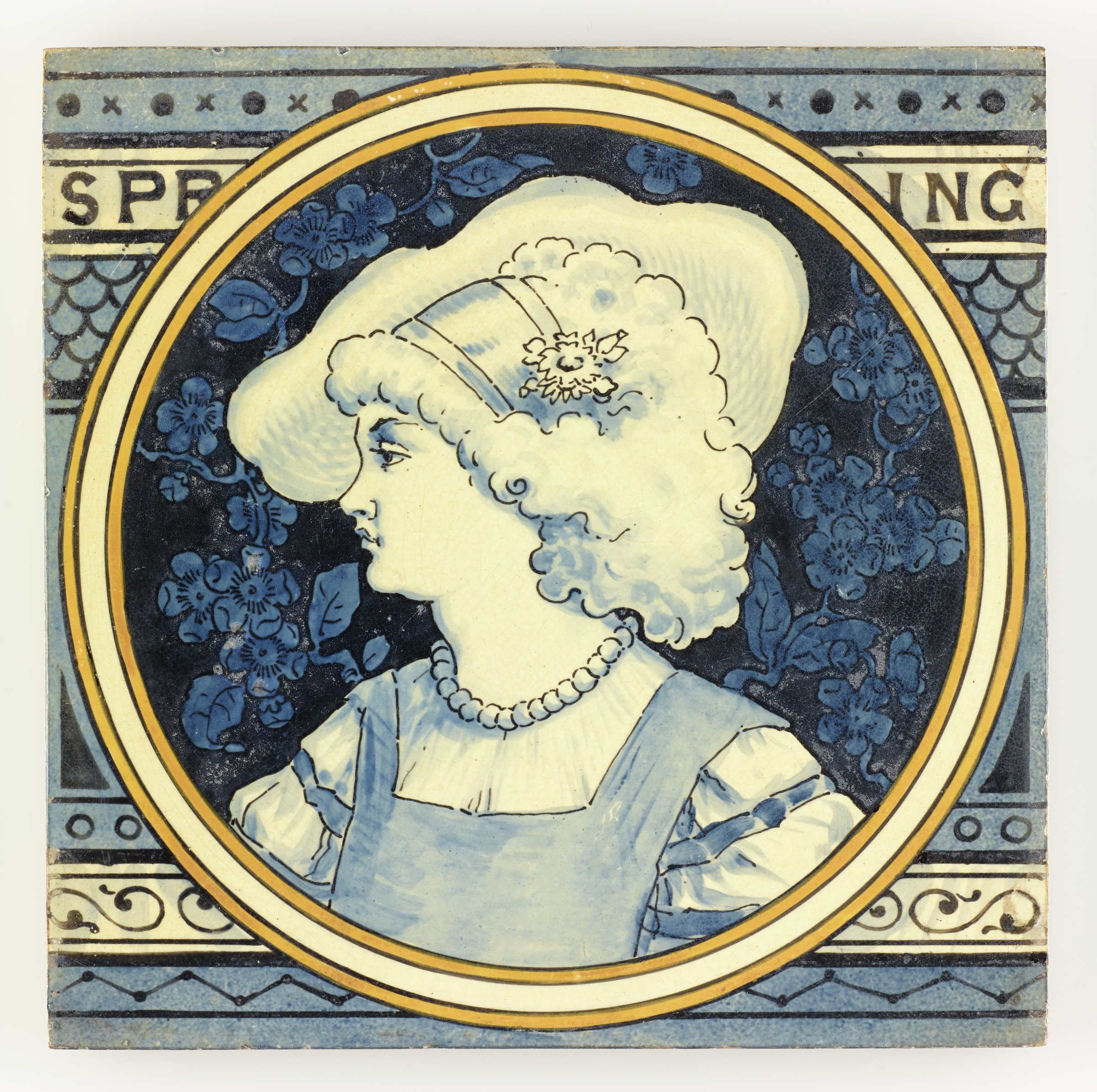 Large, square earthenware tile partially printed and hand-painted with a circular reserve outlined by a white band within two yellow bands containing in white with blue highlights the portrait of a woman to left wearing a light blouse and apron with straw hat and hairband with flower, the ground with a blue on blue design of floral vines, the larger ground of the tile contains in various shades of blue a pattern of decorative, horizontal bands with from the top a band of small x's and solid dots; the name of the season SPR ING; a fish scale pattern; a band of open dots; a band of scrolling motifs; and a band featuring a zigzag design, the reverse with horizontal bars in relief to aid adhesion when setting the tile.