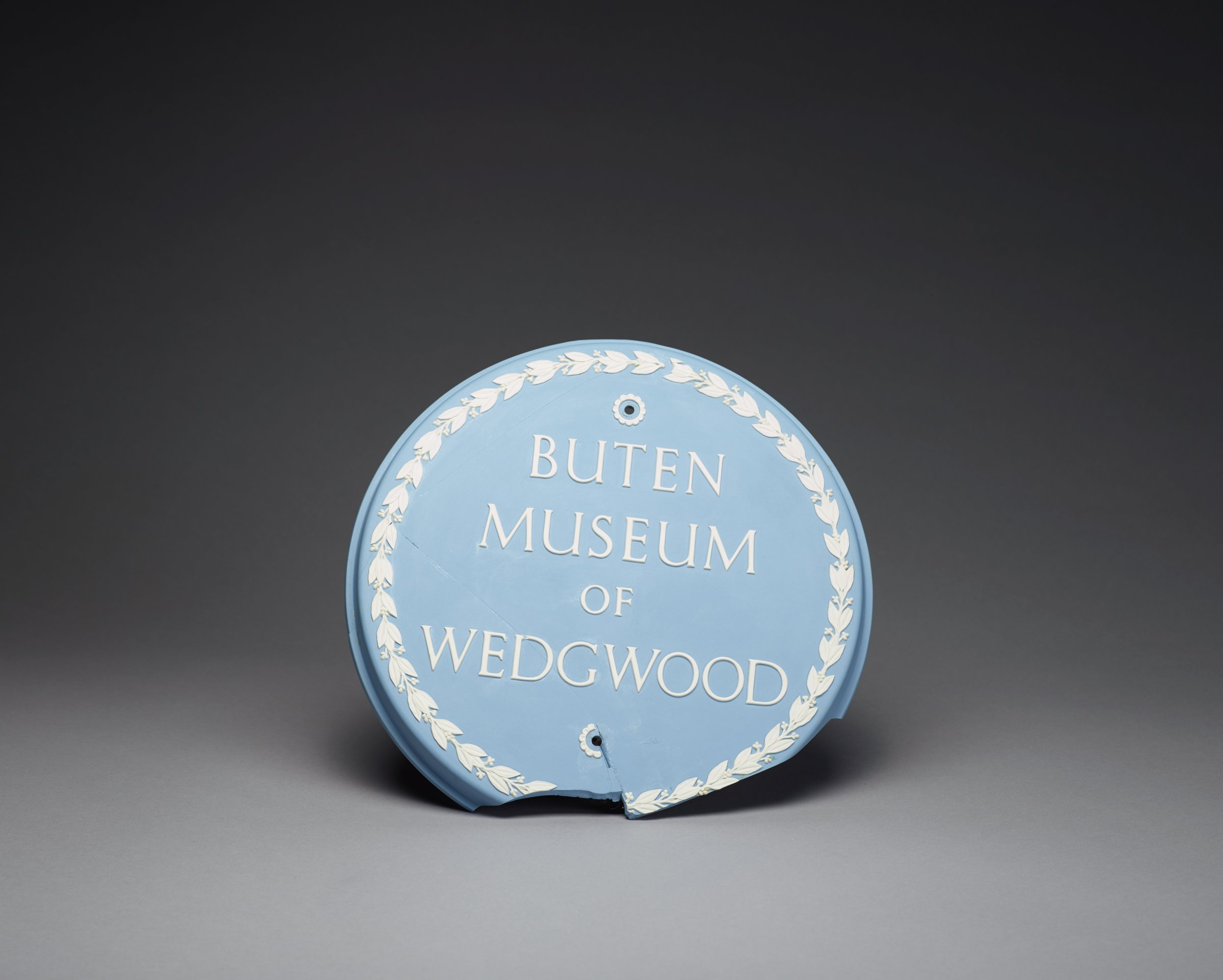 """Round plaque of solid blue jasper with border of leaves and berries in white relief, in the center the inscription """"BUTEN MUSEUM OF WEDGWOOD"""" in white relief and with two holes with flower petal borders in white relief, no doubt intended for hanging or mounting to a flat surface."""