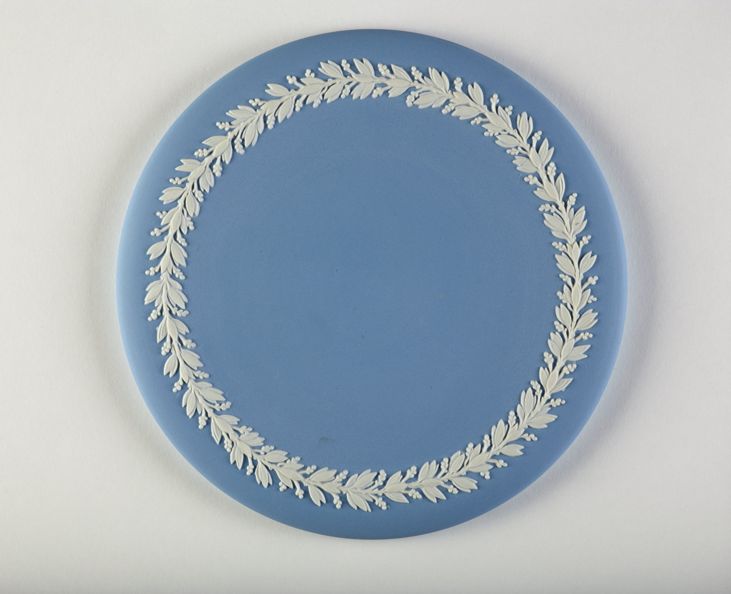 Round plaque of solid light blue jasper with border of laurel leaves and berries in white relief.