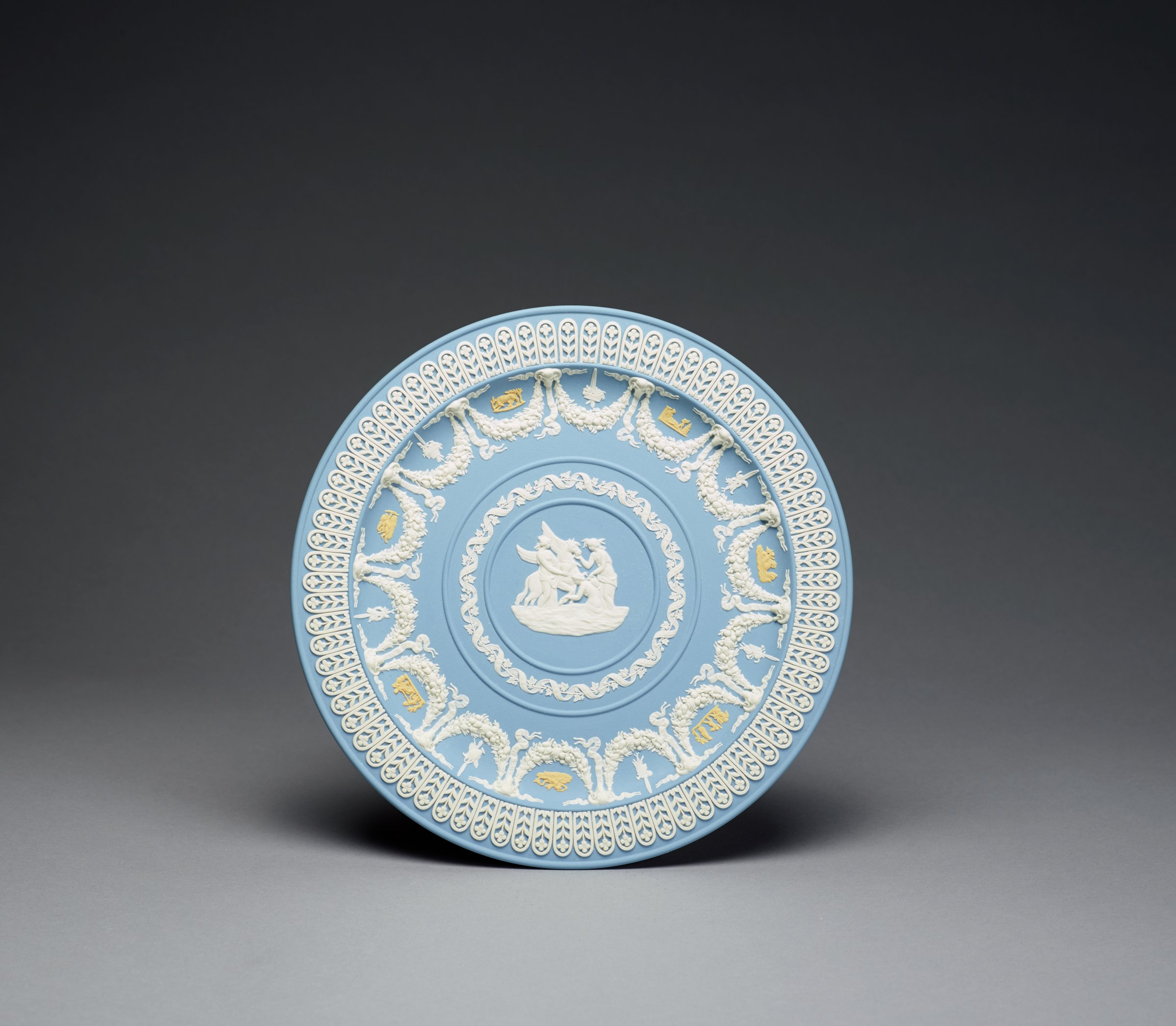 Solid light blue jasper plate with white and yellow relief decoration (tricolor) commemorating the 200th anniversary of the creation of jasperware, the edge with a border of framed, stylized floral elements, the inner well with heavy garlands hanging from ram's head masks with banners on either side and hanging below, between the garlands in yellow relief are small scenes of cupids and animals alternating with hanging trophies in white relief, in the center a band comprised of a ribbon encircling a leafy vine that encloses a relief scene of the Muses Watering Pegasus.