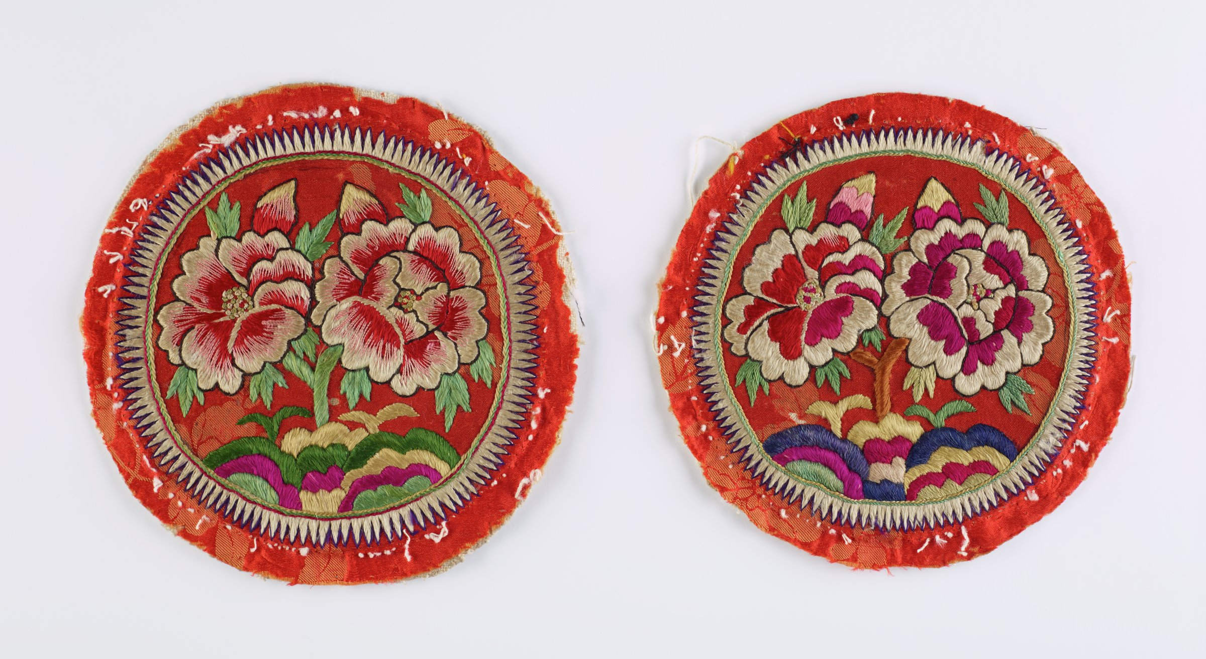 Pair of round pillow ends with embroidered Peony designs on an orange background