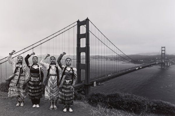 Black and white photograph with four Native American women, each with one fist raised; Golden Gate bridge in background.