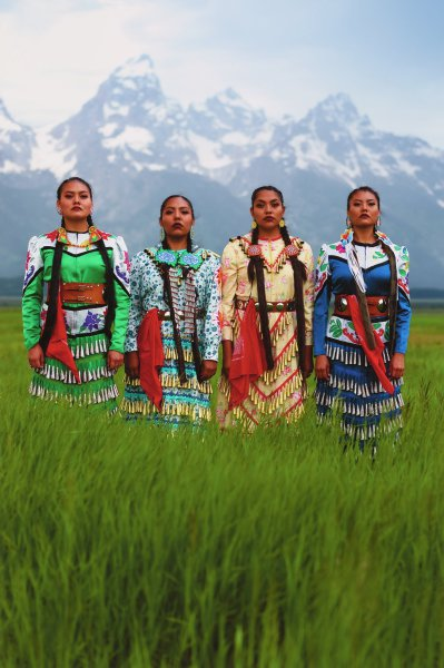 Color photograph;  four Native American women wearing jingle dresses stand in field with Grand Tetons in background