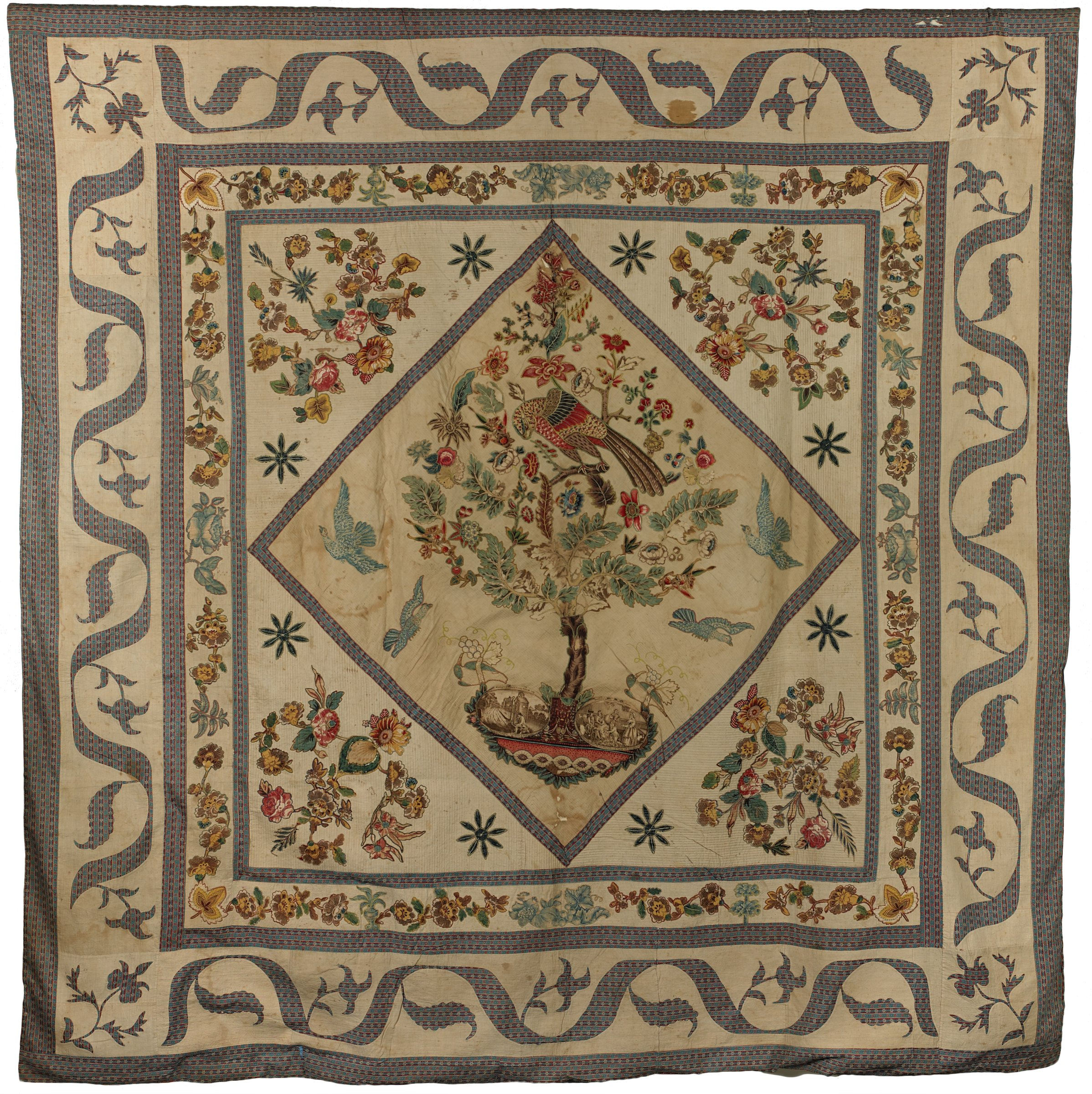 """Large bedcovering, or quilt top, of English cotton chintzes and stripes, and copperplate printed fabrics, with dozens of individual leaves, flowers and birds fastened with buttonhole stitches to a white ground in an applique method known as """"broderie perse,"""" the main design forms the Tree of Life pattern with an oversized parrot perched on a limb at the top of the tree, the trunk springs from a bowl containing two ovals of copperplate-printed fabric with the inscription on one reading, """"Whittingdon at Holloway hearing bowbells ring,"""" and """"Turn down Whittingdon, Lord Mayor of Great London,"""" and on the other, """"Whittingdon presents his cat a V--,"""" and """"Whittingdon brought Poor Puss and delivered her to the captain with tears in his eyes,"""" embroidered grape clusters are paired with long-beaked birds with appliqued heads and wings, four additional birds fly in the background, each corner of the central medallion is decorated with a different composition of flowers and leaves, the border appliqued of flowers and leaves between one single striped and one double striped border, the outermost border in reverse applique with scrolls, leaves and flowers, and finished with a final frame of four stripes."""