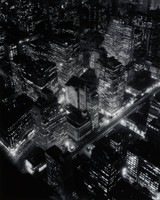 """A black and white photograph of a night time aerial view of New York city. The framing of the photograph shows many metropolitan tall buildings; the many white rectangles indicate the rooms lit from within. Below the buildings, street lamps appear as small bright white circles. In the background towards the top of the photograph, it becomes difficult to make distinction between where one building ends and the other begins while the lit windows give an illusion of floating white rectangles. A set of diagonal train tracks run between the tall buildings. The photograph was taken from the Empire State building was part of the Federal Arts Project funded the artist's """"Changing New York"""" documentary project, for which more than three hundred photographs were produced."""
