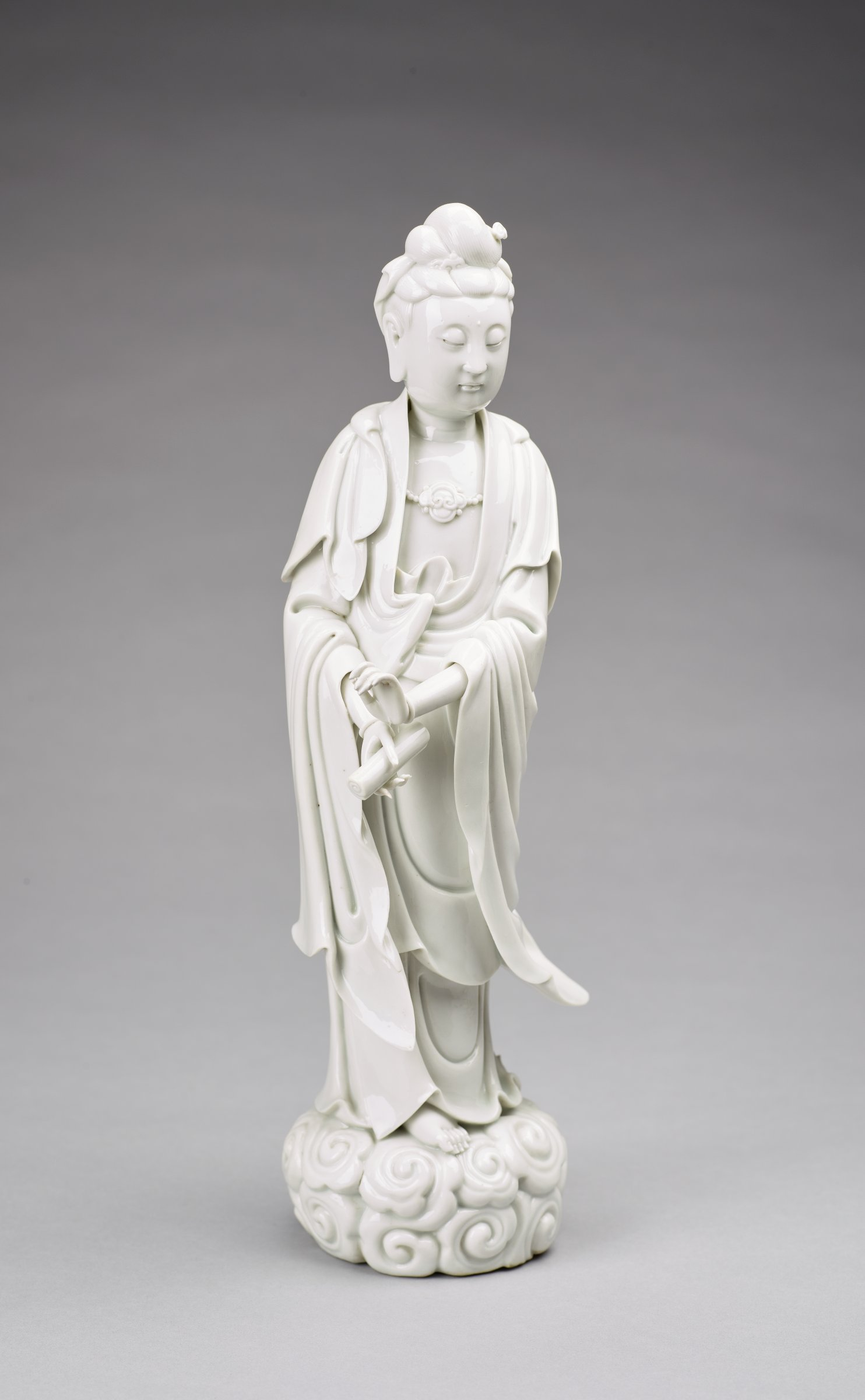 Standing figure of Guanyin on clouds, holding a scroll.