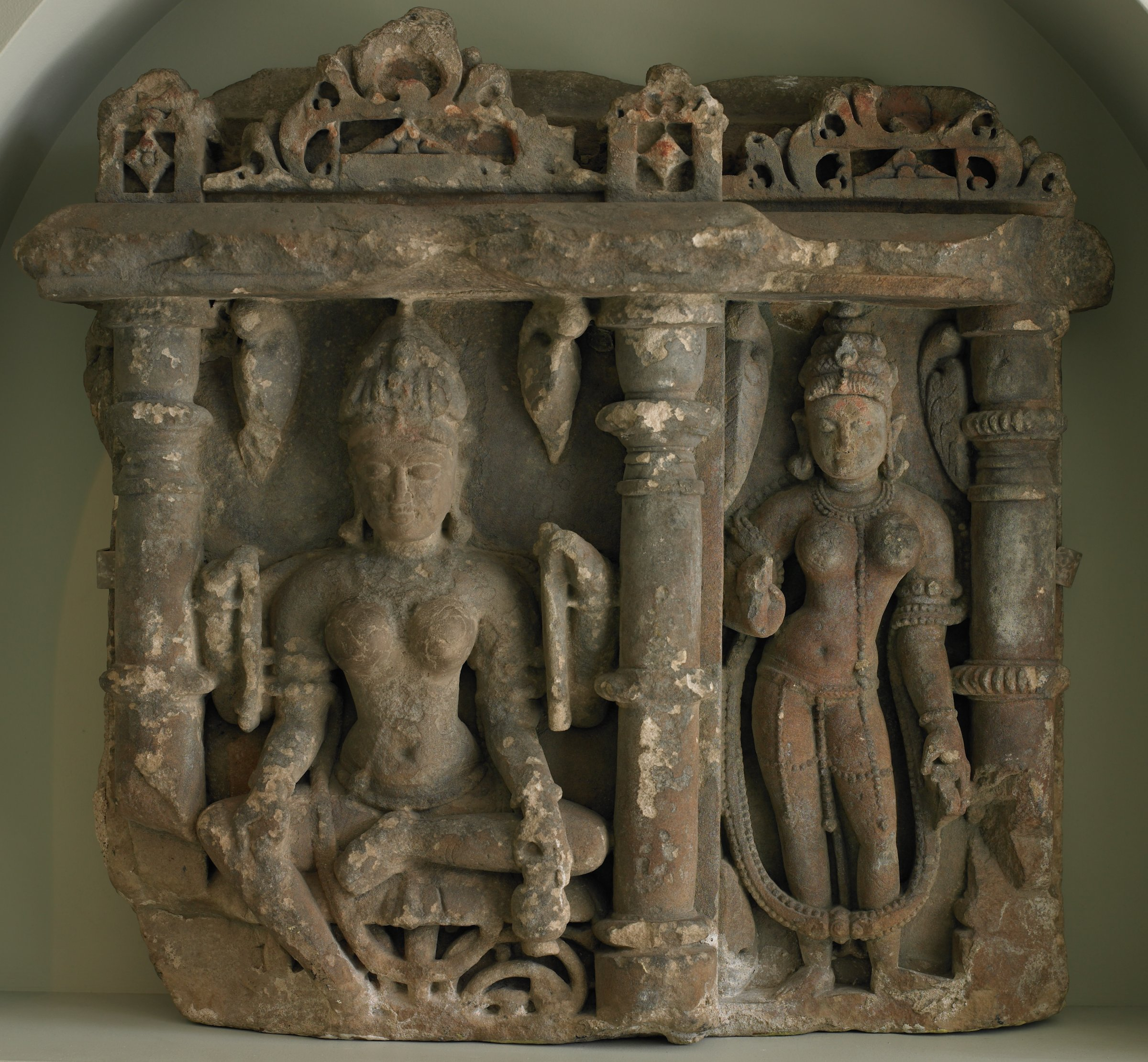One four-armed Goddess seated upon a lotus leaf with one leg pendant, hodling a water pot in lowered proper left hand and one standing goddess each in an architectural niches flanked by columns ornamented with amalaka fruit underneath moon windows (Chandrasala)