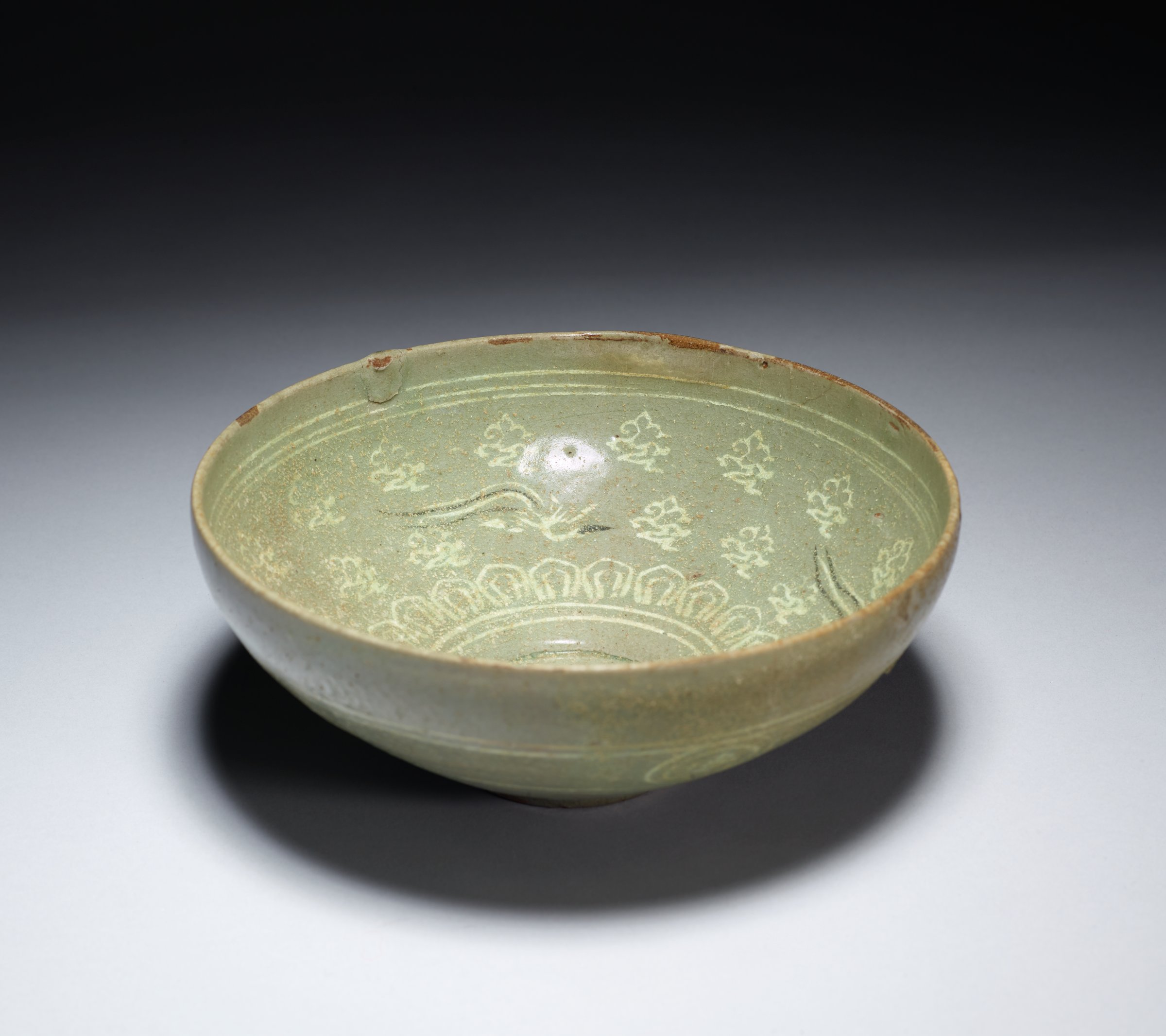 Slightly over fired inlaid celeadon bowl decorated with inlaid clouds and flying Ho Ho birds.