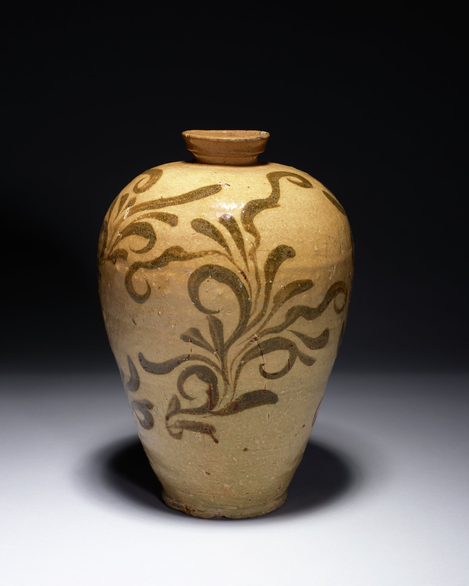 Vase with black foliate design on red clay body with clear and colored glazes. Repaired chip in lip. lightweight
