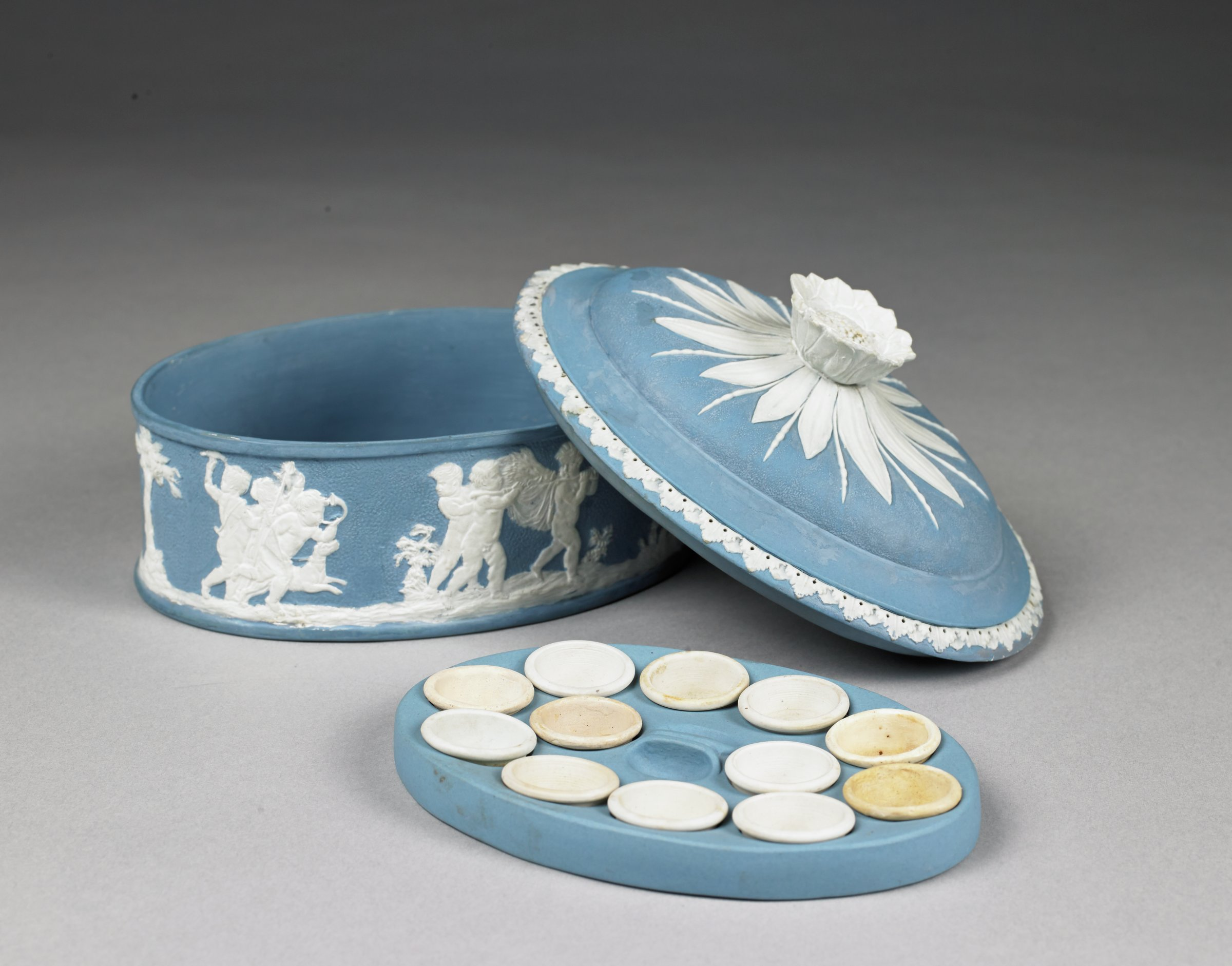 """Ladies' covered paint box of light blue and white jasperware, oval in shape, the main body with stippled ground and decorated in relief with scenes from """"Setting Out on the Hunt,"""" """"Bringing Home the Game,"""" and """"The Arts,"""" with groups of putti with dogs and hunting accoutrements, carrying game, and playing instruments, the slightly domed cover with acanthus border and sunflower finial with applied leaves against stippled ground; the interior outfitted with a blue jasper holder with twelve holes to hold paint cups and fourteen small white jasper paint cups."""