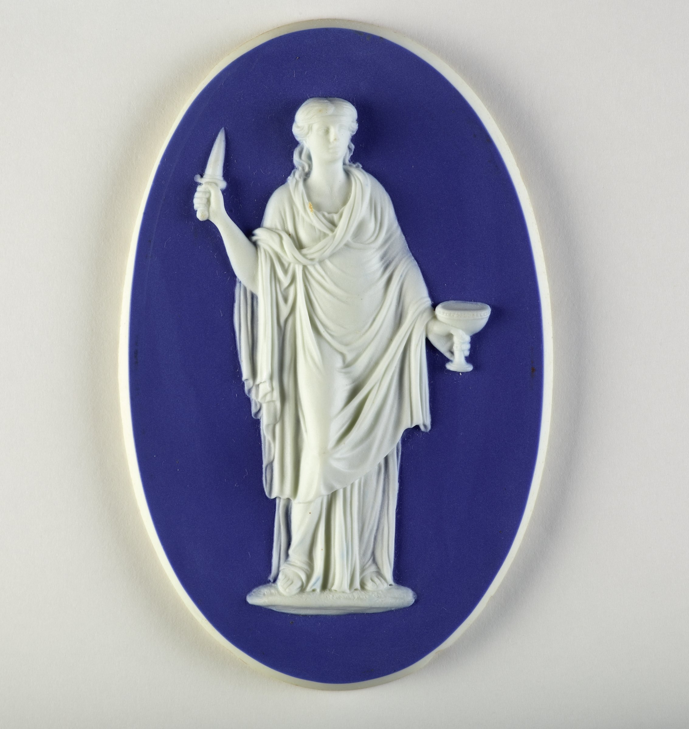 Oval medallion of white jasper with dark blue jasper dip and in white relief the figure of the Muse of Tragedy Melpomene classically dressed and with dagger and cup.