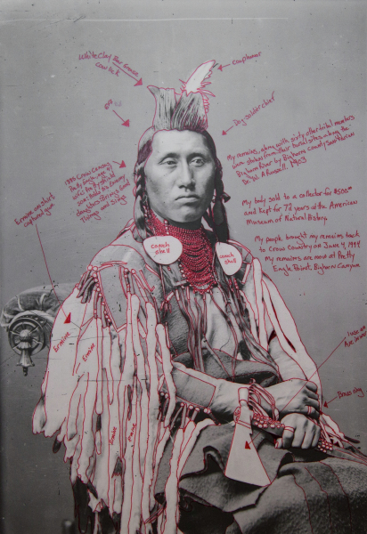 Artist-manipulated digitally reproduced photograph by C.M. (Charles Milton) Bell; subject is Déaxitchish / Pretty Eagle seated, partial figure, three-quarter view, head facing front. Elements of regalia outlined in red; text annotations in red radiate from figure.