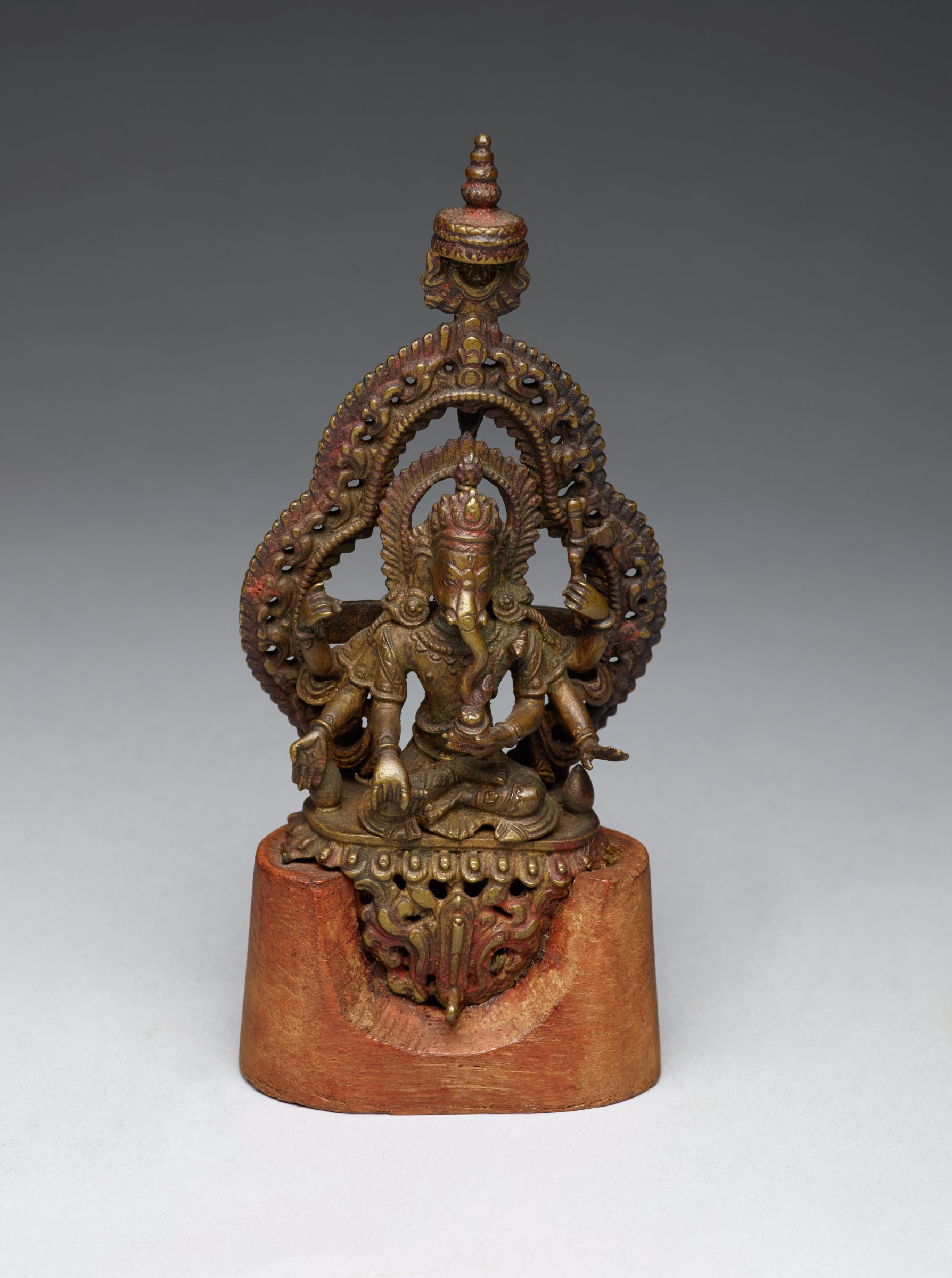 Seated elephant-headed figure with six arms, on lotus base, in front of ornate nebula topped by canopy; figure is mounted on small wooded base, and shows traces of vermilion - evidence of devotion.  A detailed cast in the round, with openwork in nebula