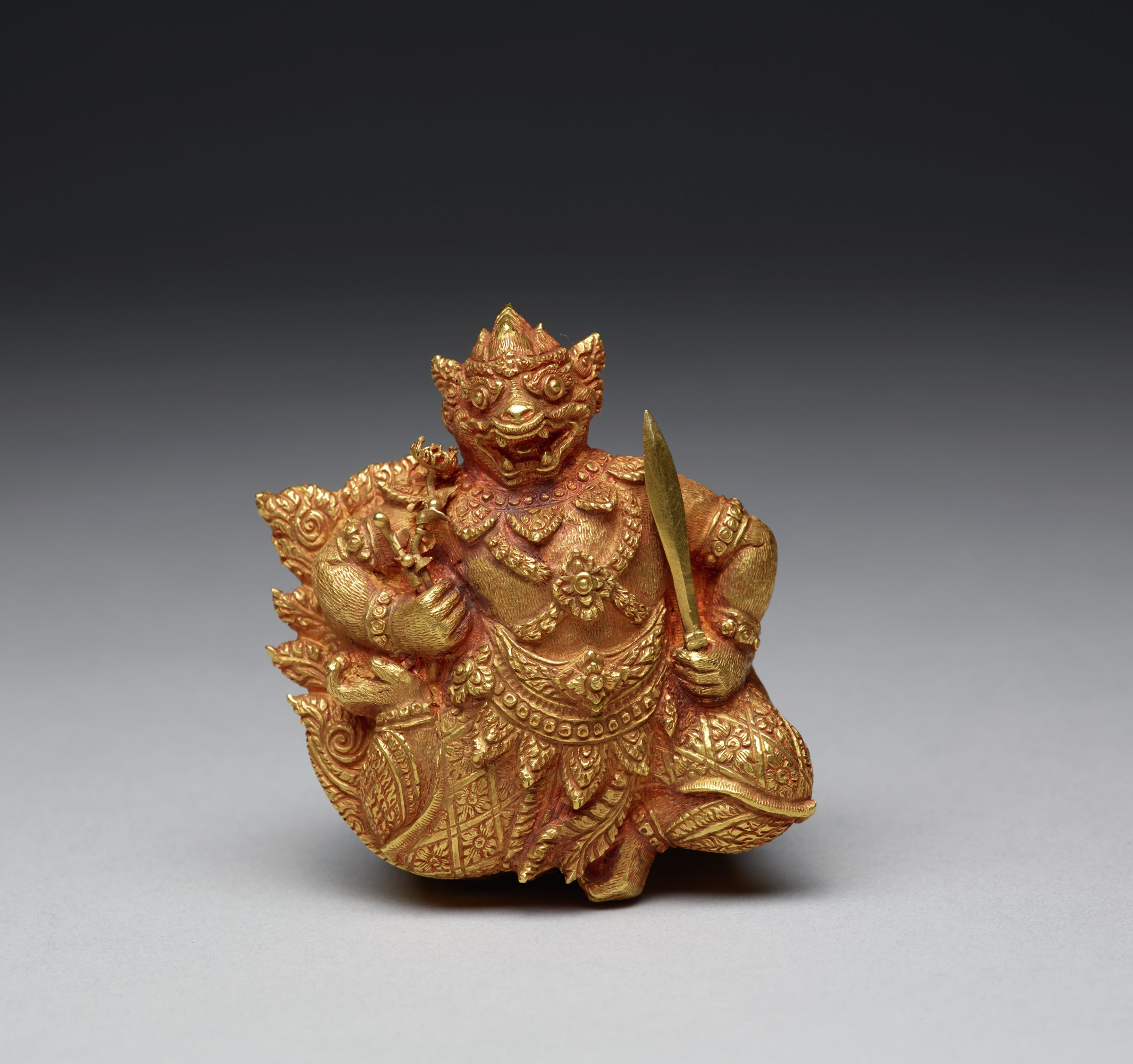 The posture of this figure, both legs bent one behind, the other underneath, signals this monkey is flying. He holds in his left hand a double-edged sword, while his right hand holds a flower. The flower may here represent the herbs required to heal Lakshman (Pra Lak) from a life-threatening wound. Hanuman is only the lid of this exquisite box. The sides of the box are lavishly decorated with birds, crabs, lobsters, mollusks, fish, birds, and diverse plants, suggesting his long journey and ability to fly over land and swim in water. This box might have been employed for luxury ingredients for a betel chewing gift exchange for honored guests.
